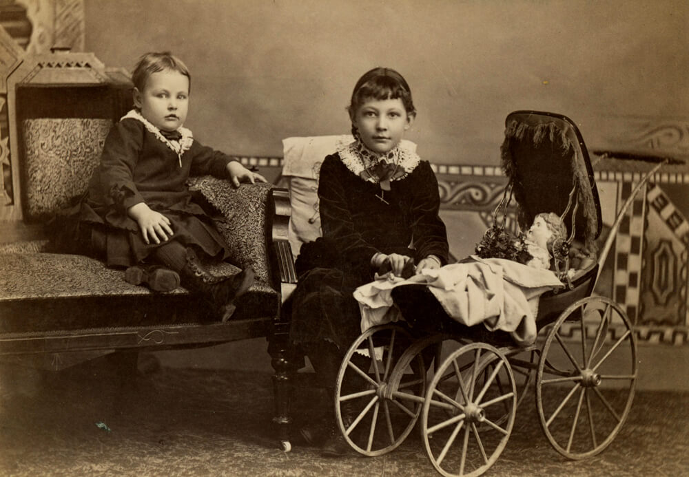 The portrait is of two young girls with doll, covered by a blanket, laying in their baby buggy. The photograph was taken in Shenandoah, Iowa (ca. 1890). Courtesy of State Historical Society of Iowa