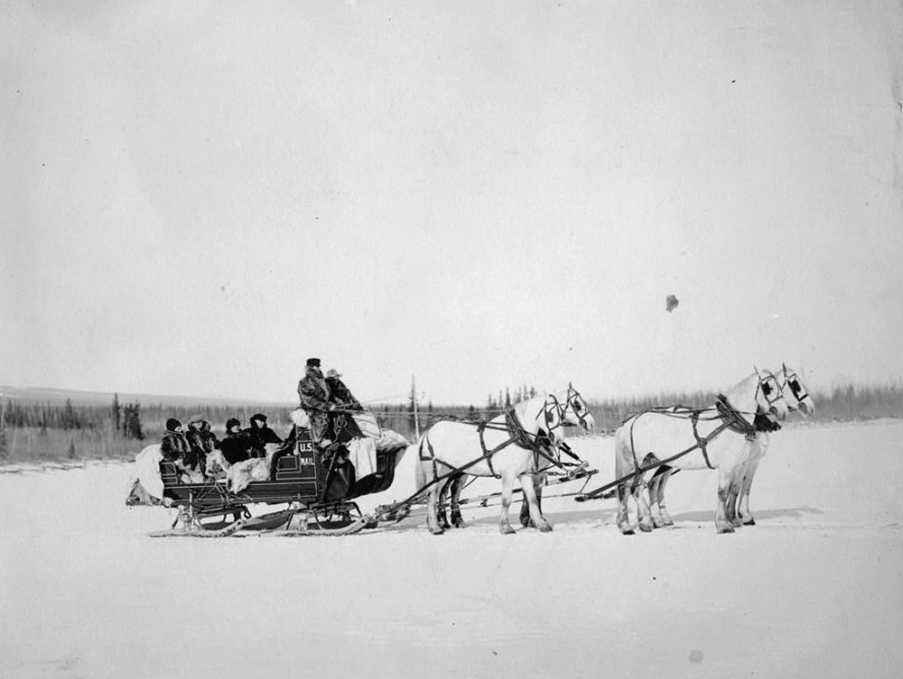 A team of horses pulls a U.S. Postal Service mail sled with postal carriers in Alaska.
