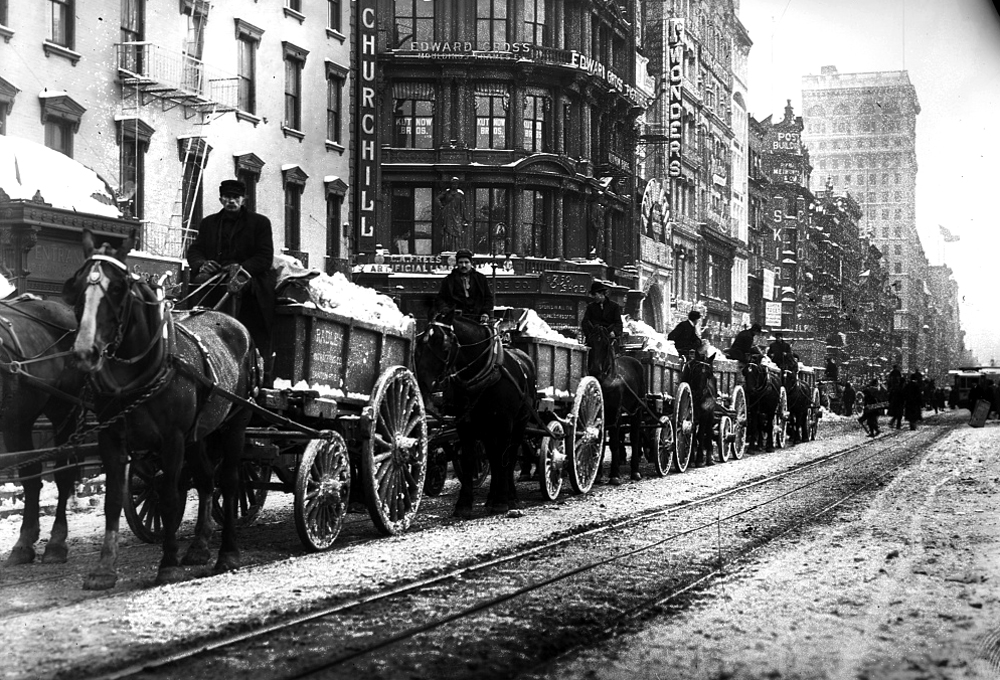 This image shows a line of several horse-drawn wagons hauling snow down a  New York City street.