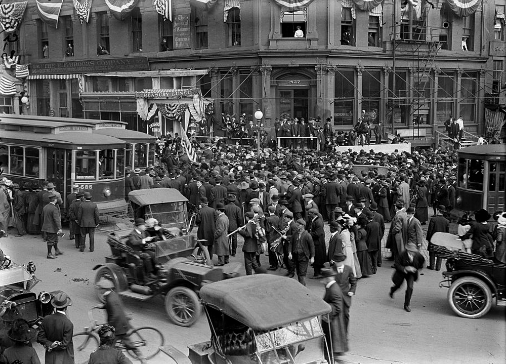A crowd gathers on a busy intersection in Washington, D.C. and trolley cars, automobiles, a bicycle are shown in the photograph.