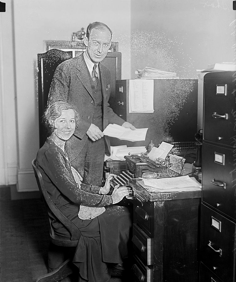 A man and a woman pose in an office with a typewriter.