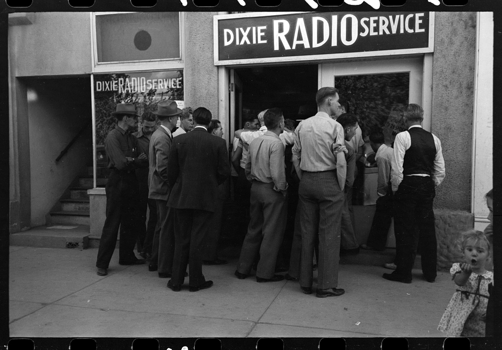 A crowd of men gather outside a radio shop to listen to the World Series game.