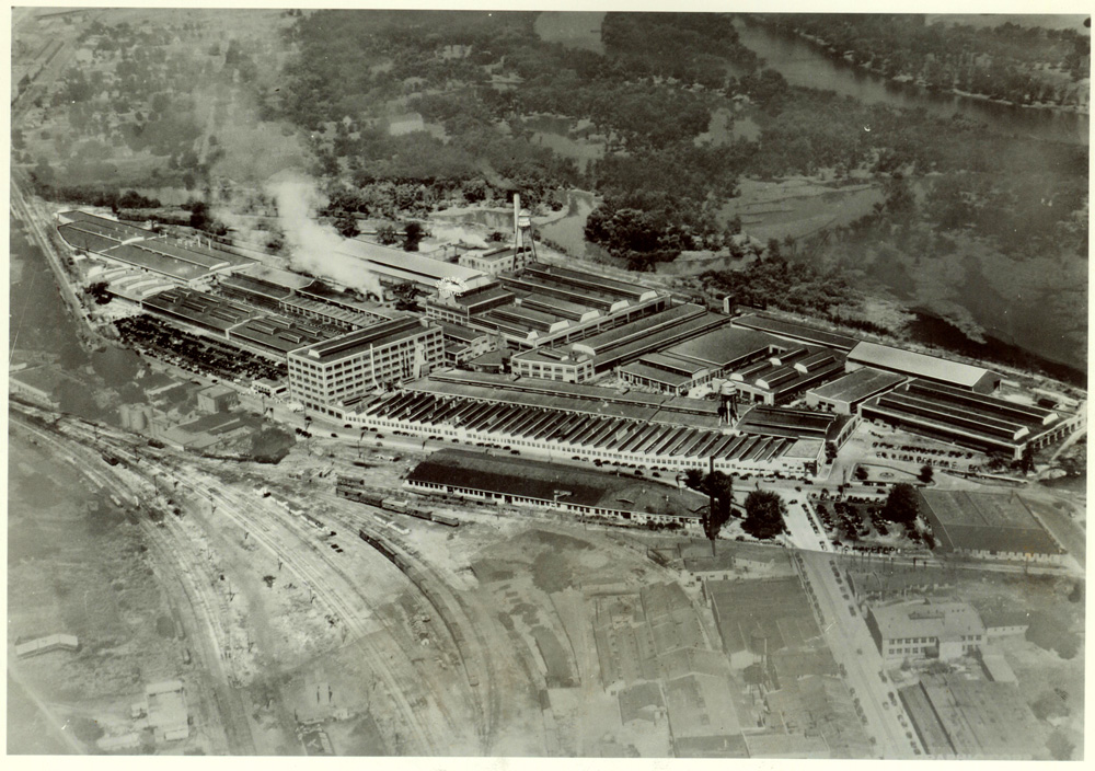 Aerial photograph of a large manufacturing facility.  More than fifteen buildings are visible within the complex, and it even has two water towers.  A network of railroad lines are in the foreground, and a river is in the background.