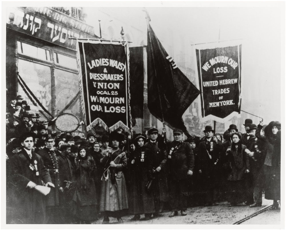 The black and white photograph shows men and women holding banning stating they mourned the loss of those who died in the fire.