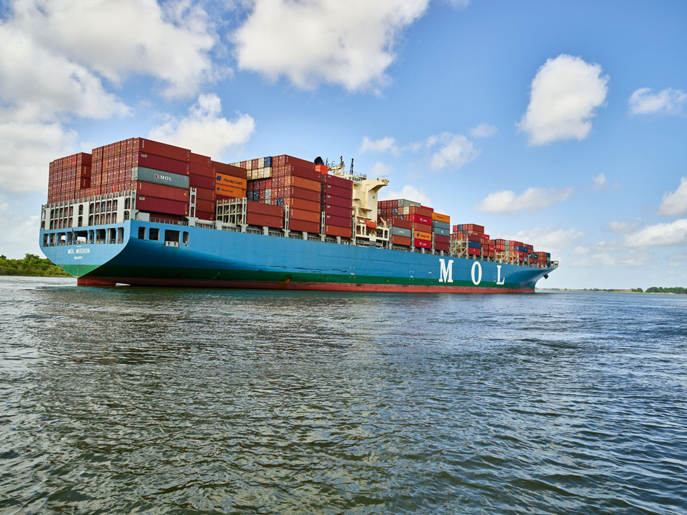 """Color photo of a loaded cargo ship navigates the Savannah River.  """"MOL"""" is visible on the side of the ship."""