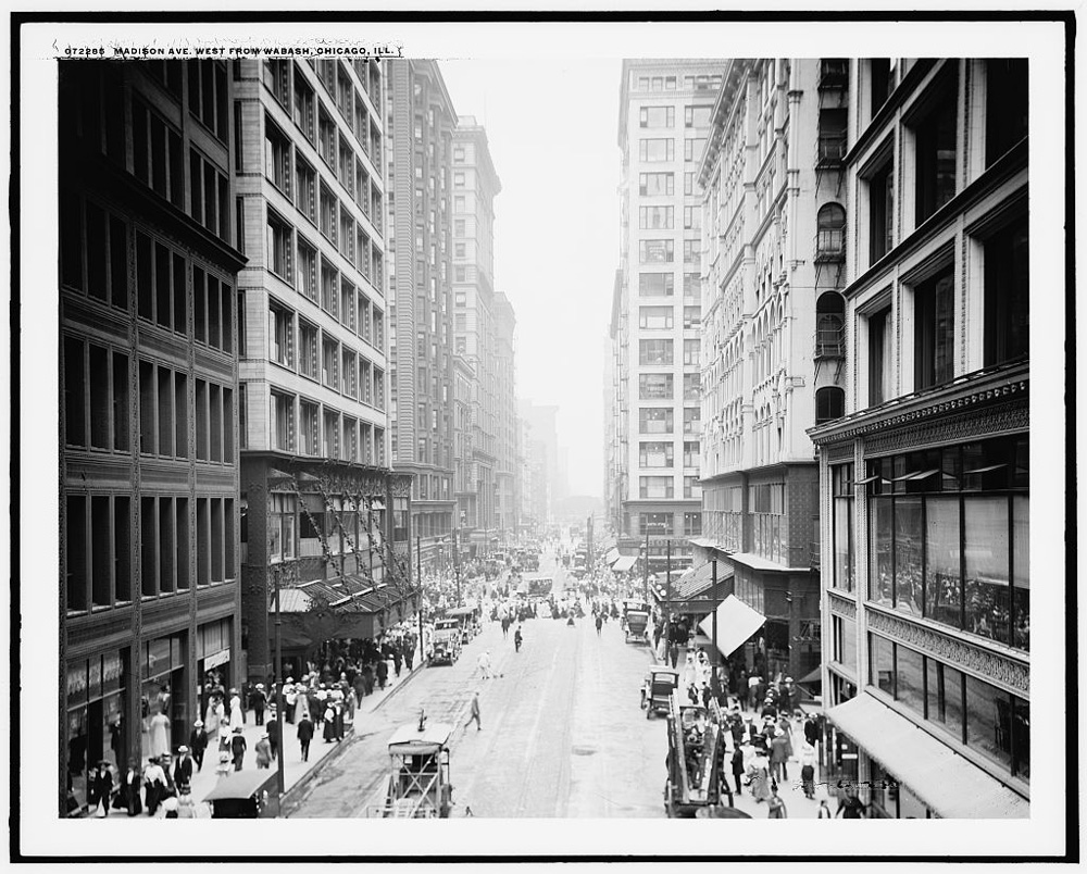 Skyscraper-lined street with pedestrians on both sides, parked cars, and moving vehicles also visible.