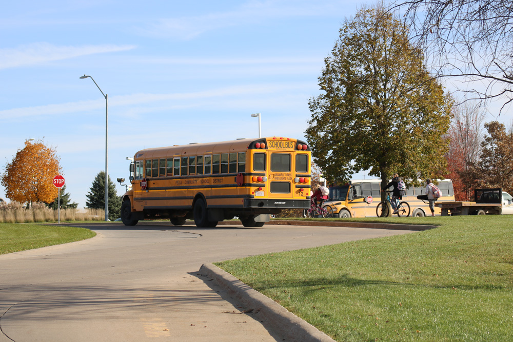 Two school busses in Pella, Iowa, 2018.  One bus is about to pull out onto the street and the other bus is about to turn into the school drive.  Two kids riding bicycles and another student standing on the sidewalk are also visible.