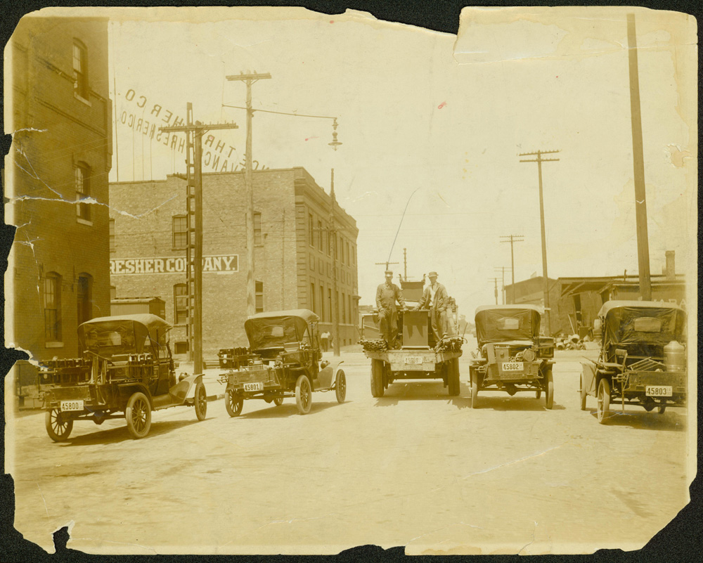 """Four """"Model T"""" roadsters and one Peerless Truck parked on a Des Moines street.  Electrical poles and brick buildings are also visible."""