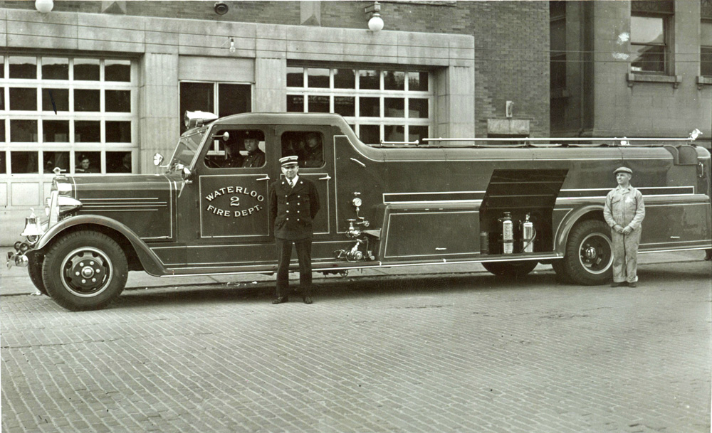 Waterloo Fire Department displays their new fully enclosed fire truck.  The new truck is parked outside the fire station, along with two men standing near it.