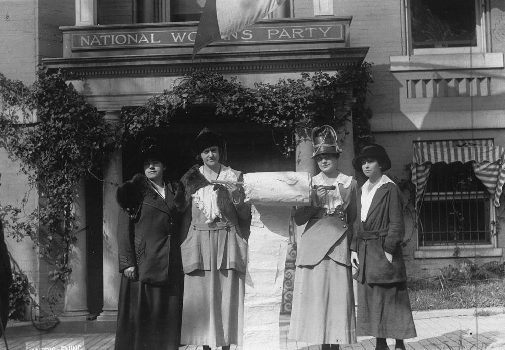 "Four women in dresses and hats proudly stand in front of a building with a sign that reads ""National Women's Party.""  Between the two women in the center is a very large roll of paper that the women are holding up.  These National Women's Party leaders had been working to collect signatures of support on a ""mile long"" paper to present to members of Congress."