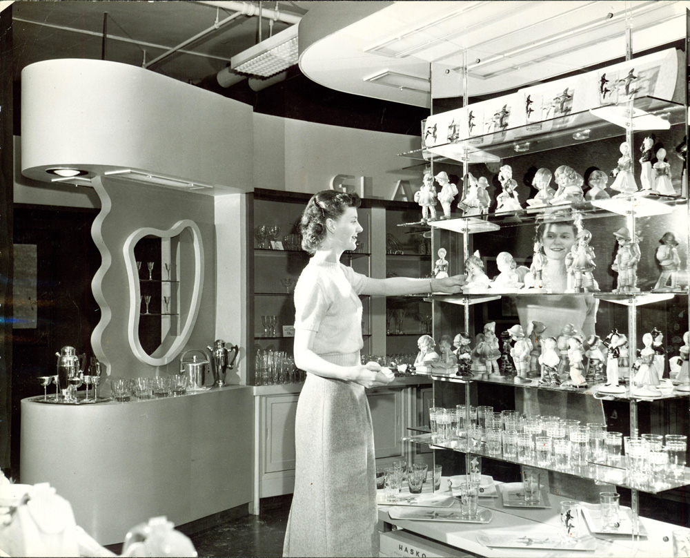 Adult woman standing in front of six-shelf display of glassware in J.C. Penny department store.