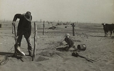 Dust bowl farmer raising fence to keep it from being buried under drifting sand in Cimarron County, Oklahoma.
