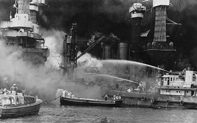 The black and white image shows the aftermath of the bombing of Pearl Harbor, Hawaii with the  USS West Virginia aflame.