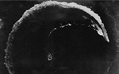 Black and white image of a Japanese battleship circling to avoid a US air attack in the Pacific.