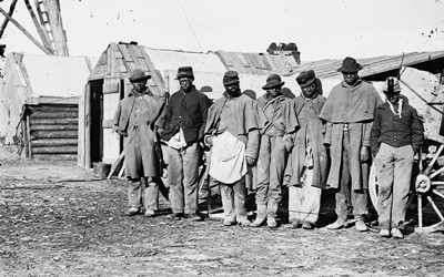 "One of the Civil War photographs compiled by Hirst D. Milhollen and Donald H. Mugridge, this 1864 image depicts seven ""contraband"" teamsters dressed in old Union uniforms standing near a wagon and shack."