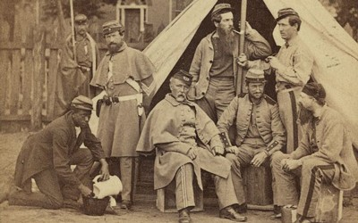 """Between 1861 and 1865 George N. Barnard and C. O. Bostwick photographed this group of white soldiers, possibly the 8th Company, 7th New York Infantry, at Washington D.C.'s Camp Cameron. An African-American """"contraband"""" kneels to the left of the group."""