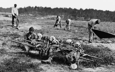 This photograph, published by John Reekie in April 1865, portrays five African-Americans collecting bones of soldiers killed in battle during Ulysses S. Grant's 1864 Virginia Overland Campaign. In the foreground an African-American squats near a stretcher filled with skulls, bones, and decaying limbs.