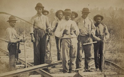 This photograph of a group of eight African-Americans constructing a railroad in northern Virginia for the United States Military Railway Department was taken by Andrew J. Russell in either 1862 or 1863. Most of the men can be seen holding tools required for laying railroad track.