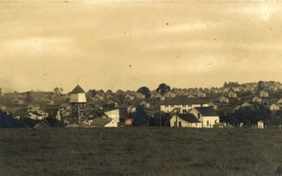 Landscape view of Buxton, Iowa, circa 1910. The photograph shows two water towers, a few two-story buildings, dozens of identical houses, along with streets of the town.