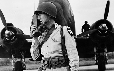 """A soldier uses a """"walkie-talkie"""" to communicate during World War II."""