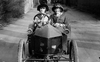 Two children ride in an early model of the automobile.