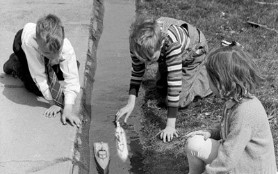 Three children play outside with toy boats in the town of Grundy Center, Iowa.
