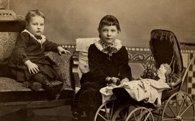 Photograph portrait of two girls with doll in baby buggy in Shendandoah, Iowa.