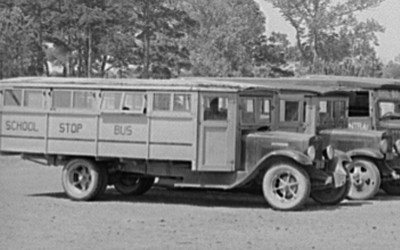 This image shows a line of parked motorized school buses that were used in the early twentieth century.
