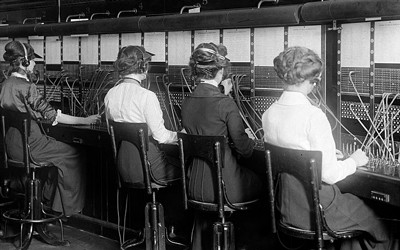This photograph shows six female switchboard operators at work.