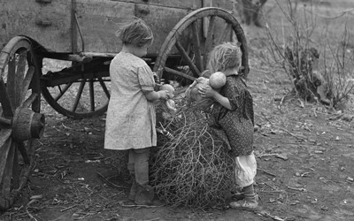 This image shows two children playing with dolls in the tumbleweed on a farm during the Great Depression.