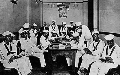 A photo of African American soldiers and sailors sitting and standing around a table in a Red Cross Rest Room specifically outfitted for only African Americans during World War One.  This photo was taken at the Red Cross headquarters, Branch Number 6, of the New Orleans Chapter.
