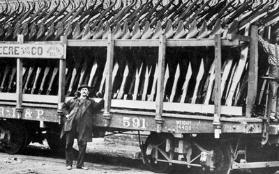 Photograph shows three men and a railroad car loaded with steel plows.  Article tells a brief narrative of Mr. John Deere.