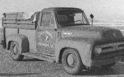 """1950s era Ford F-250 truck with """"Lee C. Norris, Freemont, IA."""" painted on passenger's door, is parked at the Des Moines airport awaiting the flight of 39 hogs from Iowa  to Yamanashi, Japan.  Back of truck is boarded up on the sides and covered with a strapped-down tarp."""