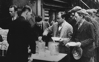 The black and white photo shows a long line of men waiting in a bread line.