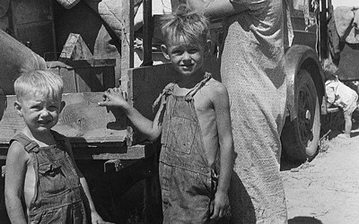 Black and white photograph of a mother and two sons behind a truck filled with their possessions.
