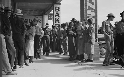 The source is a black and white photograph showing a line of men, women, and children waiting for relief checks in California.