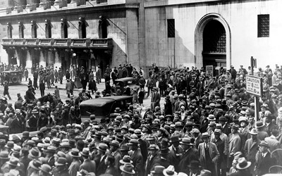 Black and white photograph of a crowd of people standing outside of the New York Stock Exchange after the stock market crash of 1929.