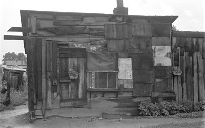 """The image of a decrepit shack that was one of many in """"Hoovervilles"""" across American during the Great Depression."""
