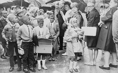 African American children on way to PS204, 82nd Street and 15th Avenue, pass mothers protesting the busing of children to achieve integration.