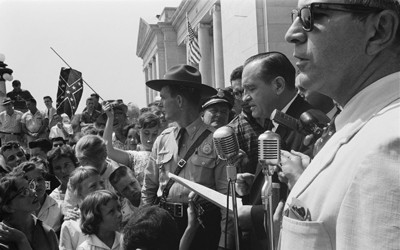 "Photograph shows a group of people, one holding a Confederate flag, surrounding speakers and National Guard, protesting the admission of the ""Little Rock Nine"" to Central High School."