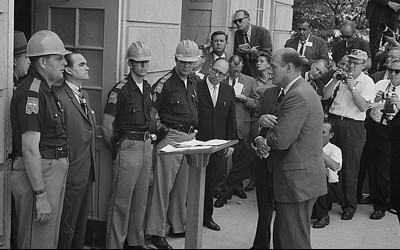 Photograph showing Gov. Wallace standing defiantly at a door while being confronted by Deputy U.S. Attorney General Nicholas Katzenbach.