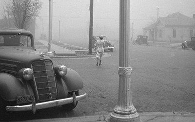 Image showing a parked car in the foreground of a town with a woman wearing a dress holding her hat on her head.  A dust storm is engulfing the town.