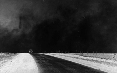 The image shows a very heavy black cloud of dust behind a single car that is driving on a country road.