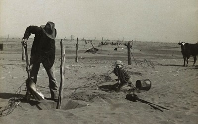 The image shows a farmer digging up a fence and attempting to move it higher to prevent it from being buried in the dust that is accumulating around it.  There is a young boy on his knees close by.