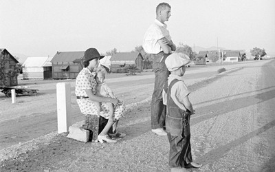 This image shows a family of three - father, mother and young son - waiting on the side of the road.  According to the title, they are relocating to California.