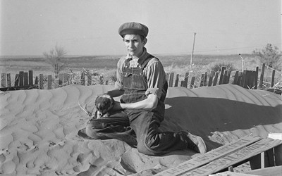 Image shows a young boy holding what appears to be a football sitting on top of a very large dune of dust.  It looks like he is sitting on a sand dune in a desert.