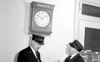 "Union Pacific railroad conductors are checking the time on the ""Standard Time"" clock and pocket watch in 1950"