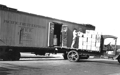 Man loading fruit onto refrigerated rail car.
