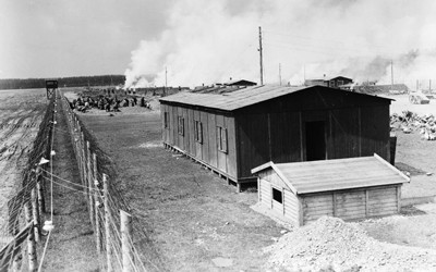 Image shows a small building with barbed wire fencing around it.  It is an image of a concentration camp in Germany.