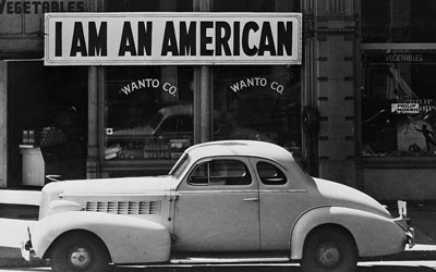 """A large sign reading """"I am an American"""" placed in the window of a store in a black and white image."""